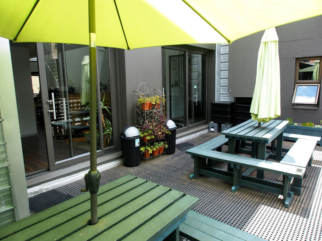 Outdoor terrace with green benches and yellow umbrellas