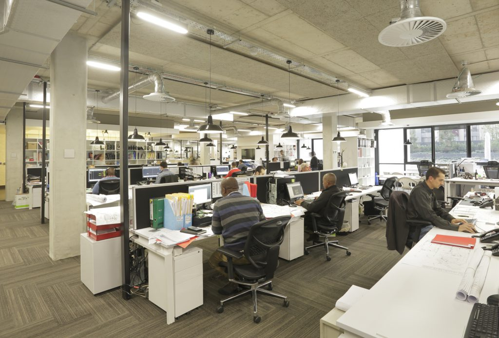 Occupants at their desks in a well-lit, open-plan office environment